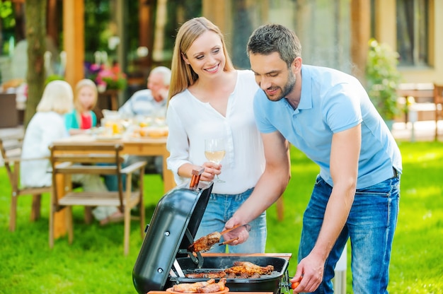 Barbecue familial. joyeux jeune couple faisant griller de la viande sur le gril tandis que d'autres membres de la famille sont assis à la table à manger en arrière-plan