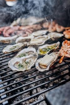 Barbecue de fruits de mer au barbecue. collection de poulpes, huîtres, palourdes, crevettes tigrées grillées sur grill