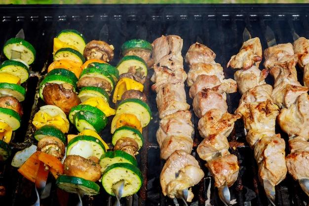 Barbecue fumant sur la viande et les légumes grillés.