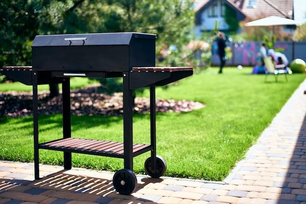 Barbecue grill sur roues avec supports en bois dans le jardin