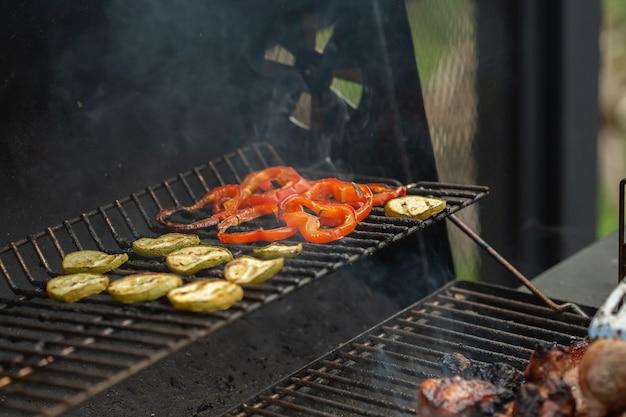 Un barbecue avec des légumes sont grillés sur un feu ouvert.