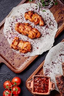 Barbecue de poulet servi avec du sumakh et des herbes sur un pain au lavash.