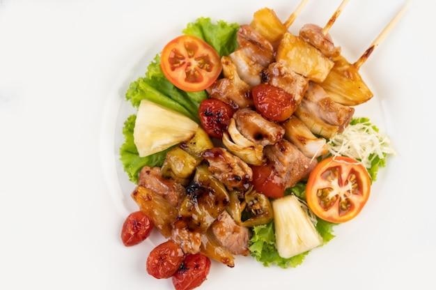 Barbecue avec une variété de viandes, avec tomates et poivrons sur une plaque blanche.