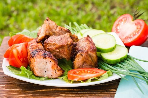 Barbecue de viande et de légumes frais sur une assiette sur une table en bois
