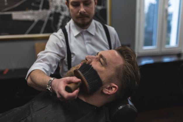 Barber balayant les cheveux du visage du client