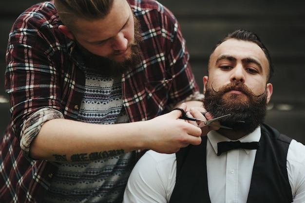 Barber avec des ciseaux pour retoucher une barbe