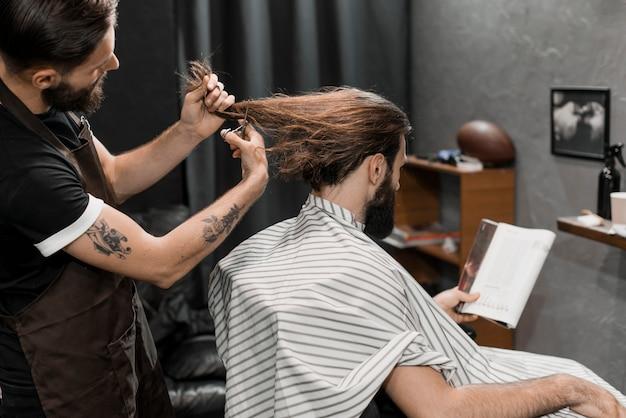 Barber coupe les cheveux longs de l'homme dans un salon de coiffure