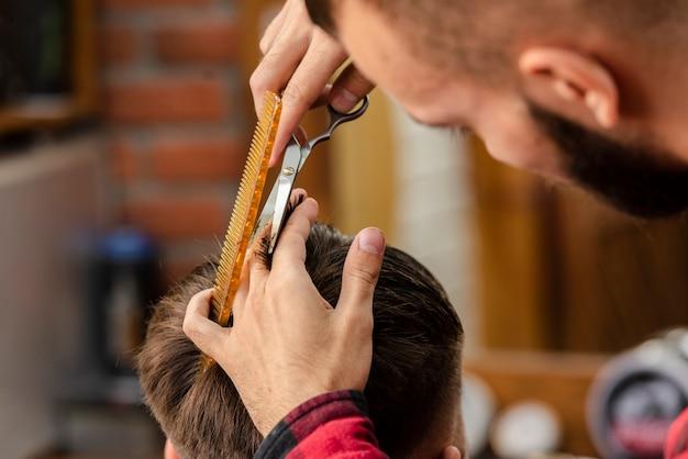 Barber coupe avec des ciseaux et un peigne