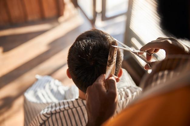 Barber couper les cheveux du client avec des ciseaux dans le salon de coiffure