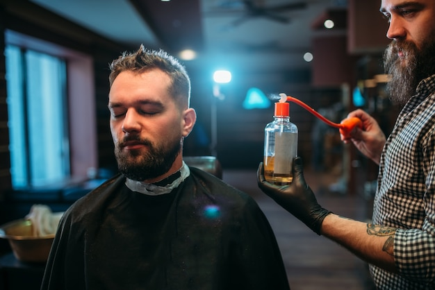 Barber éclaboussant le visage du client par une lotion après-rasage