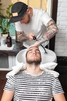 Barber essuyant la tête de son client avec une serviette
