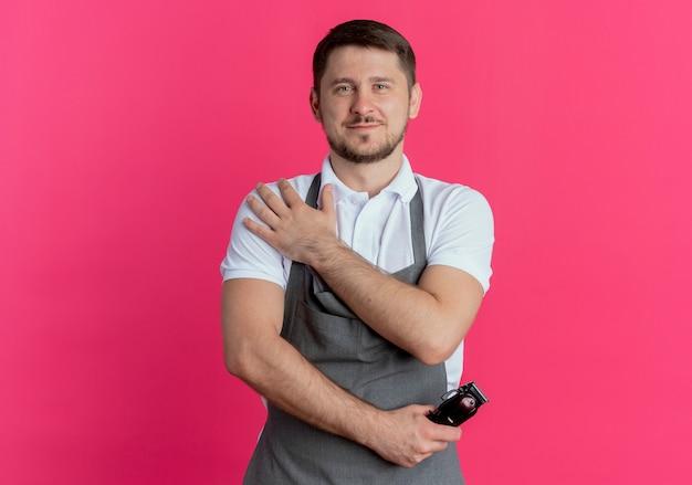 Barber man in apron holding tondeuse à barbe regardant avec une expression confiante debout sur fond rose