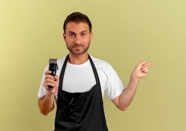 Barber man in apron holding trimmer pointant avec l'index sur le côté à la confiance debout sur mur léger