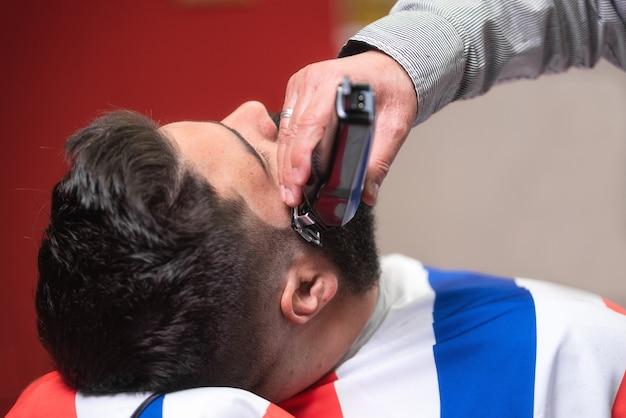 Barber rasant la barbe d'un bel homme barbu avec un rasoir électrique au salon de coiffure.