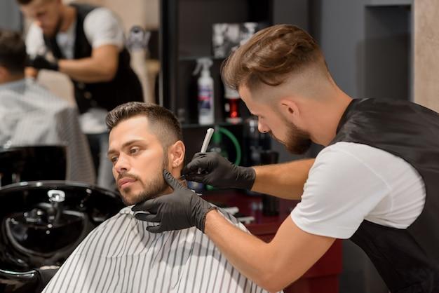 Barber s'est concentré sur le rasage de la barbe de l'homme à l'aide d'un rasoir pointu.