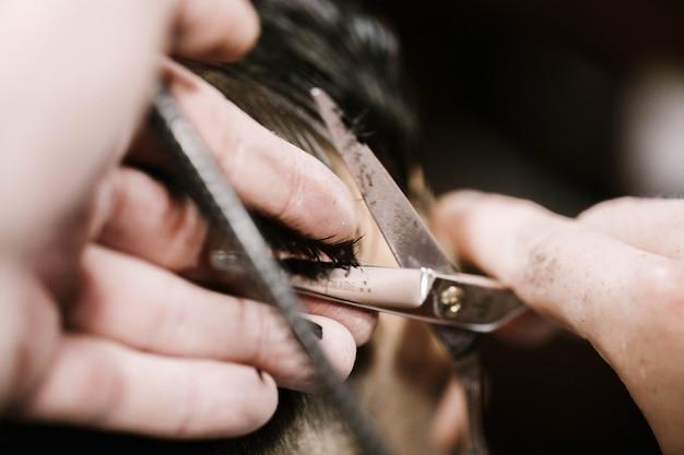 Barber tient les cheveux de l'homme dans les doigts alors qu'il coupe