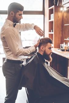 Barbier au travail. vue latérale d'un jeune homme barbu se faisant couper les cheveux par un coiffeur assis sur une chaise au salon de coiffure