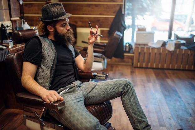 Barbier barbu brutal en chapeau avec un rasoir à la main assis dans une chaise en cuir
