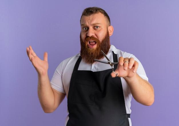 Barbier barbu professionnel en tablier tenant des ciseaux à bras levé à la confusion et mécontent debout sur le mur violet