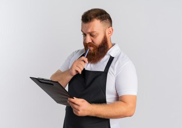 Barbier barbu professionnel en tablier tenant le presse-papiers en le regardant avec un visage sérieux pensant debout sur un mur blanc