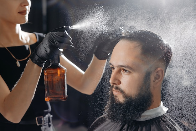 Barbier femme coupe les cheveux à un homme barbu.