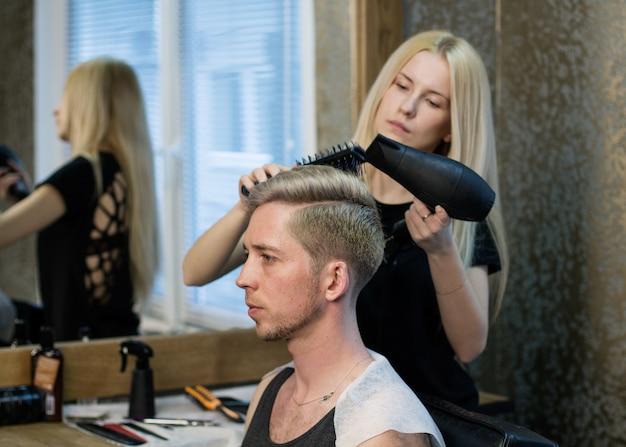Barbier femme séchant la coupe de cheveux de l'homme