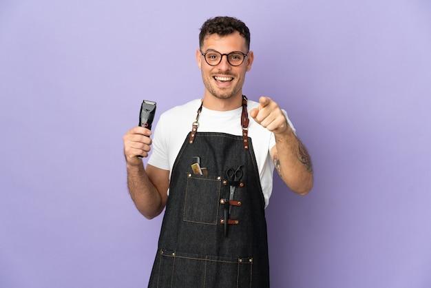 Barbier homme caucasien dans un tablier isolé sur violet surpris et pointant vers l'avant
