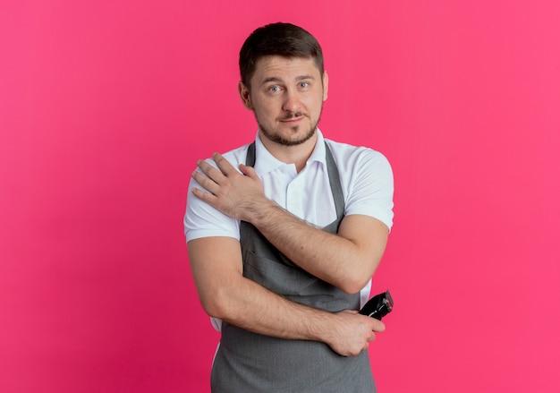Barbier homme en tablier tenant tondeuse avec une expression confiante sérieuse debout sur un mur rose