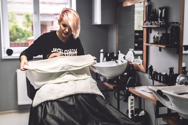 Barbier mettant une serviette sur le visage du client