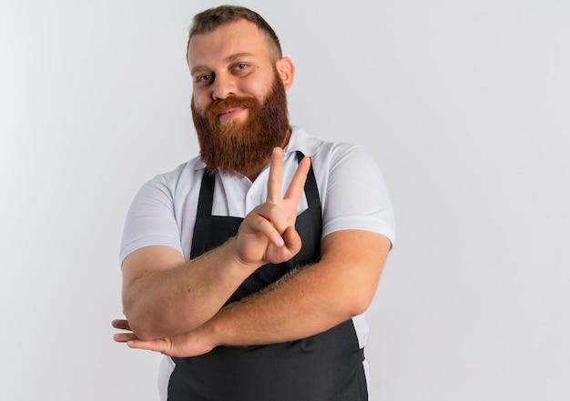 Barbier professionnel barbu en tablier souriant joyeusement montrant la victoire chanter debout sur un mur blanc