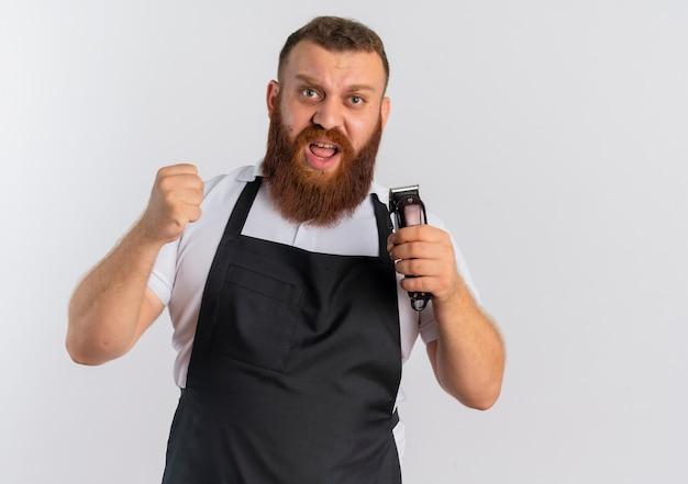 Barbier professionnel barbu en tablier, tenant la machine à couper les cheveux serrant le poing avec le visage en colère frustré debout sur un mur blanc