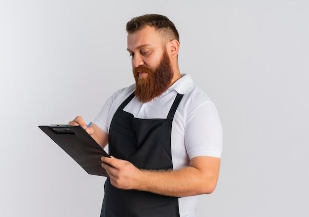 Barbier professionnel barbu en tablier tenant le presse-papiers en le regardant avec un visage sérieux debout sur un mur blanc