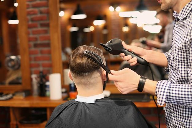 Barbier professionnel travaillant avec le client dans un salon de coiffure