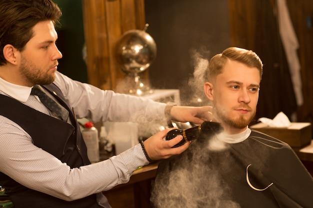 Barbier professionnel travaillant dans son salon de coiffure