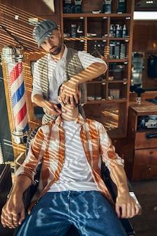 Barbier sérieux tenant un rasoir droit au cou de son client tout en le rasant et en regardant la caméra