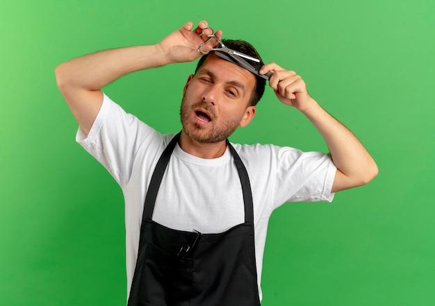 Barbier en tablier de couper ses cheveux avec des ciseaux à la confiance debout sur mur vert