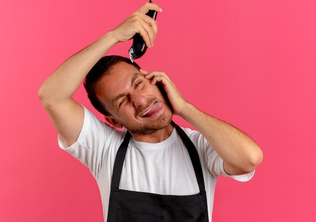Barbier en tablier de raser ses cheveux avec tondeuse qui sort la langue debout sur le mur rose