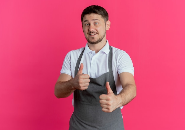 Barbier en tablier regardant la caméra en souriant montrant les pouces vers le haut debout sur fond rose