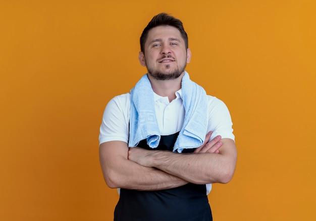 Barbier en tablier avec une serviette autour du cou lookign at camera smiling confiant avec les bras croisés debout sur fond orange