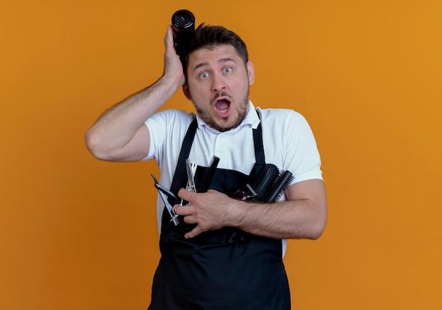 Barbier en tablier tenant des brosses à cheveux, spray et ciseaux confus et surpris debout sur un mur orange