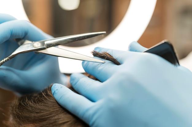 Barbier utilisant des gants en latex pour donner une coupe de cheveux au client
