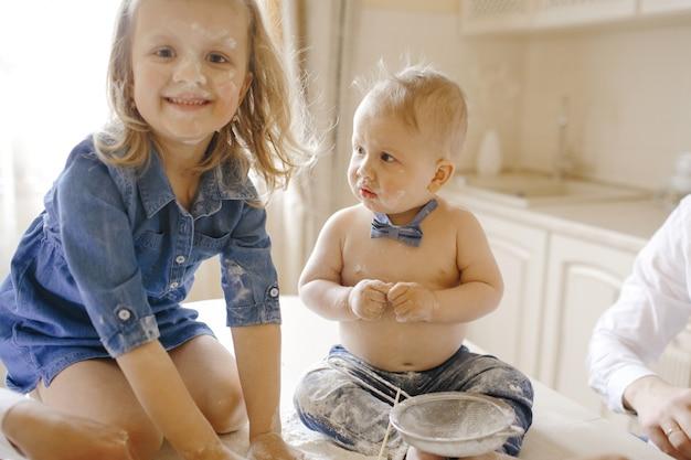 Barbouillé petit garçon et fille assise sur une table