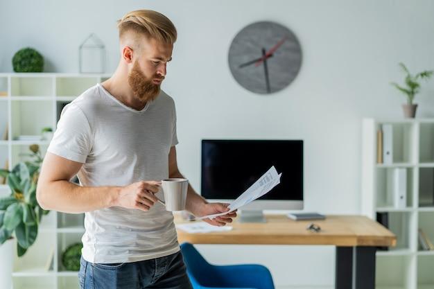 Barbu jeune homme d'affaires travaillant au bureau moderne. homme portant un t-shirt blanc et prenant des notes sur les documents.