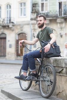 Barbu jeune homme assis avec sa bicyclette en ville