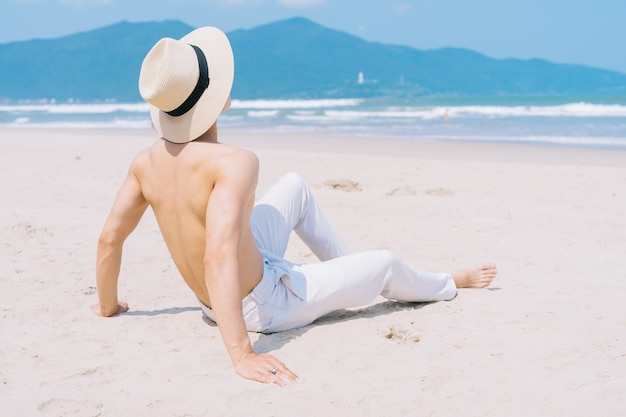 Barebacked jeune homme asiatique assis sur le sable et regardant la mer