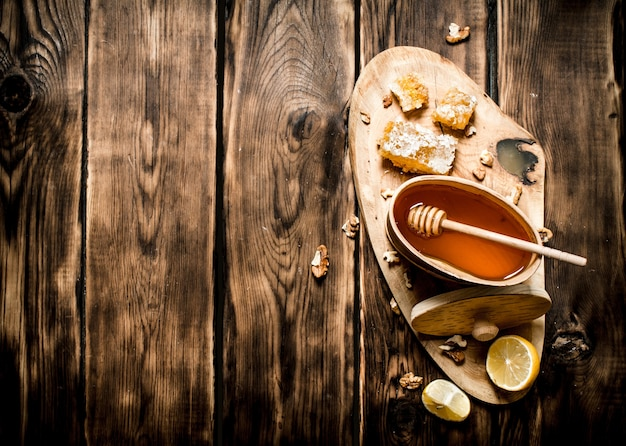 Baril avec du miel et des noix sur un tronc d'arbre. sur fond de bois.
