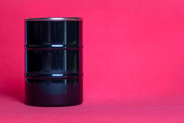 Baril de pétrole en métal sur rouge.