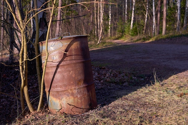 Baril rouillé dans un parc arboré
