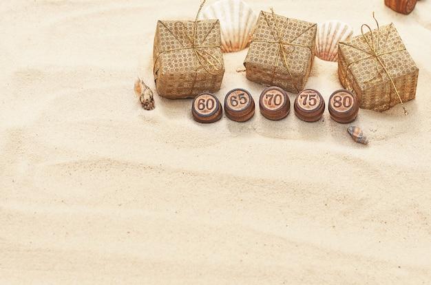 Barils en bois avec chiffres et boîtes en or sur le sable. pour les soldes d'été