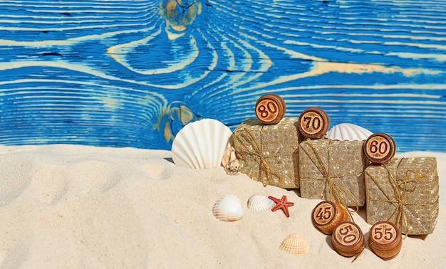 Barils en bois avec chiffres et coffrets cadeaux en or dans le sable avec coquillages pour la vente d'été